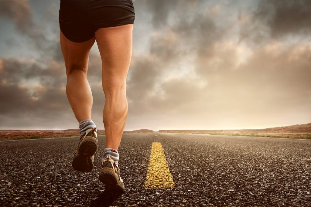 Man in 40's running along tarmac road with yellow lines in middle clouds in sky