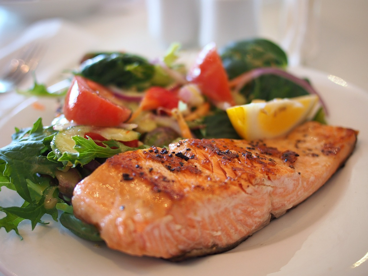 plate of cooked salmon with salad on white plate